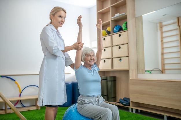 Ältere frau, die in einem rehabilitationszentrum mit ausbilder trainiert
