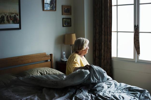 Ältere frau, die in einem schlafzimmer sitzt