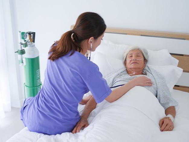 Ältere frau, die in krankenhausbett legt.