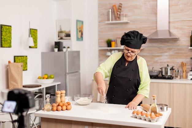 Ältere frau, die inhalte für den kulinarischen blog erstellt, der leckeres brot zubereitet. pensionierter blogger-koch-influencer, der internet-technologie verwendet, kommuniziert und blogging in sozialen medien mit digitaler ausrüstung fotografiert