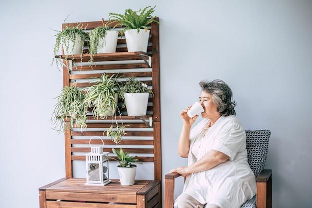 Ältere frau, die kaffee oder milch sitzt und trinkt
