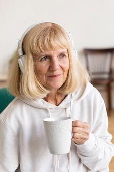 Ältere frau, die kaffee trinkt und musik über kopfhörer hört