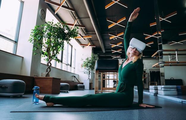 Ältere frau, die körperliche rehabilitation und pilates mit ihrem trainer im sportzentrum durchführt