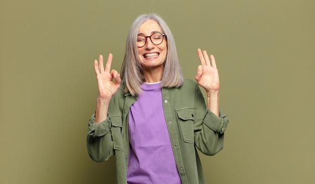 Ältere frau, die konzentriert und meditierend aussieht, sich zufrieden und entspannt fühlt, denkt oder eine wahl trifft