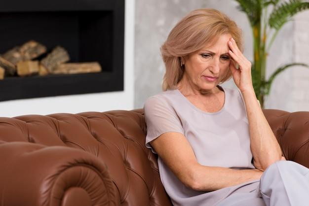 Ältere frau, die kopfschmerzen hat