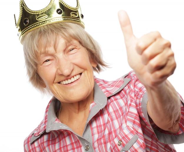 Ältere frau, die krone trägt, die funky aktion tut