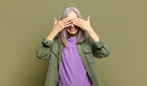 Ältere frau, die lächelt und sich glücklich fühlt, die augen mit beiden händen bedeckt und auf eine unglaubliche überraschung wartet