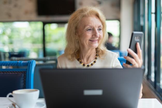 Ältere frau, die laptop-computer und handy sitzt und benutzt