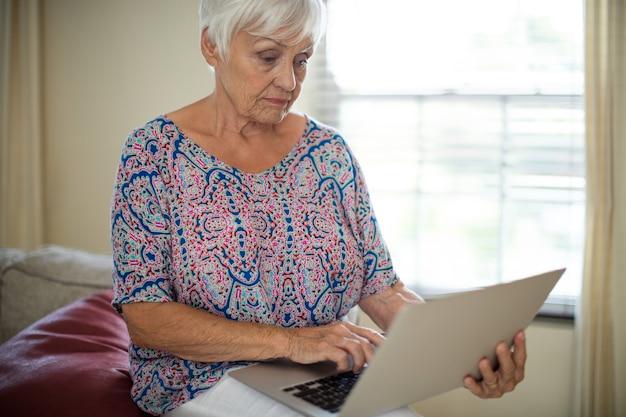 Ältere frau, die laptop im wohnzimmer zu hause benutzt