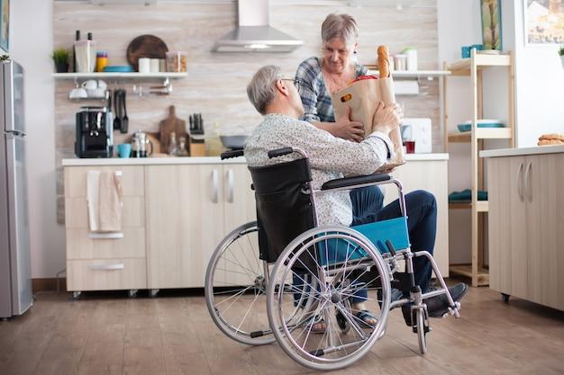 Ältere frau, die lebensmittelpapiertüte vom behinderten ehemann im rollstuhl nimmt. reife leute mit frischem gemüse vom markt. leben mit gehbehinderten menschen