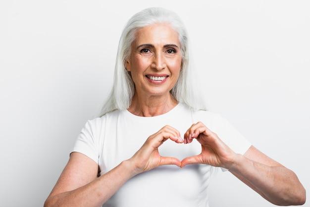Ältere frau, die liebeszeichen zeigt