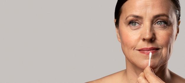 Ältere frau, die lippenstift mit wattestäbchen entfernt