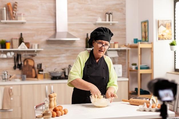 Ältere frau, die live-video für kulinarischen vlog zu hause aufnimmt