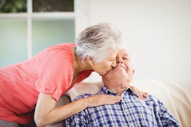 Ältere frau, die mann auf backe im wohnzimmer küsst