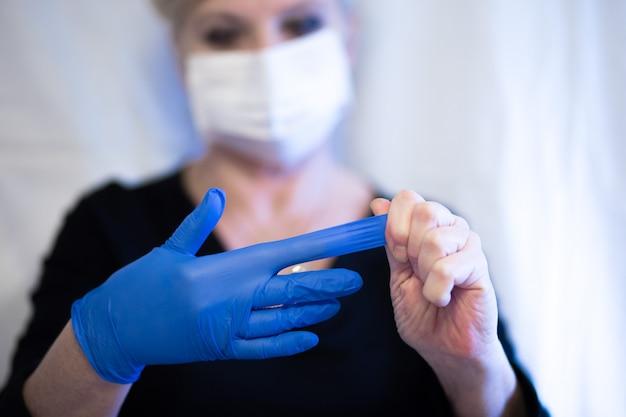 Ältere frau, die maske trägt und den handschuh von der hand entfernt. selektiver fokus. symptome von coronaviren und epidemischen viren.