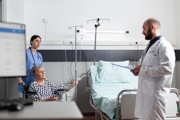 Ältere frau, die medizin durch intravenöse leitungstasche erhält, die auf einem rollstuhl sitzt, der von einer krankenschwester im krankenzimmer geschoben wird. arztstation, die nach schmerzen fragt, um die diagnose zu stellen.