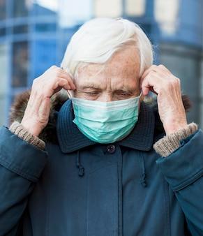Ältere frau, die medizinische maske in der stadt trägt