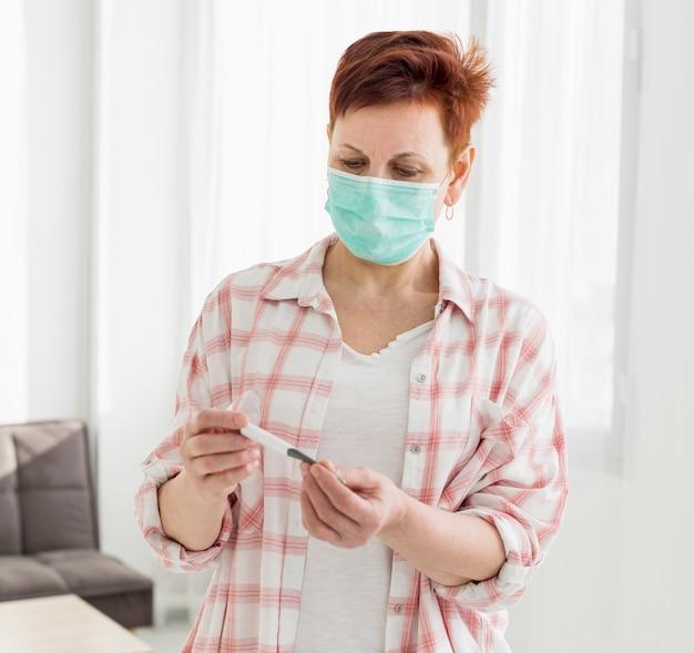 Ältere frau, die medizinische maske trägt, die thermometer betrachtet
