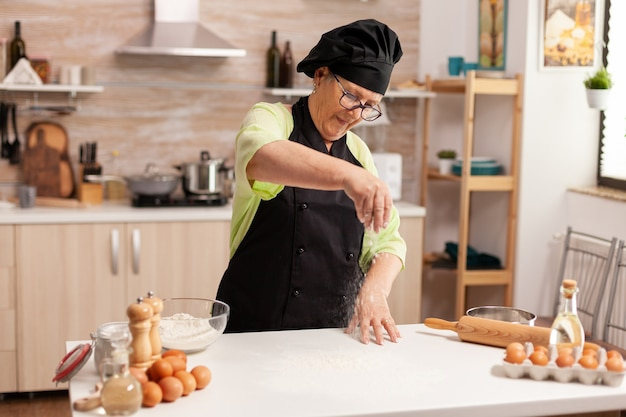 Ältere frau, die mehl verwendet, um köstliche kekse auf dem küchentisch zu hause zuzubereiten, der mehl ausbreitet
