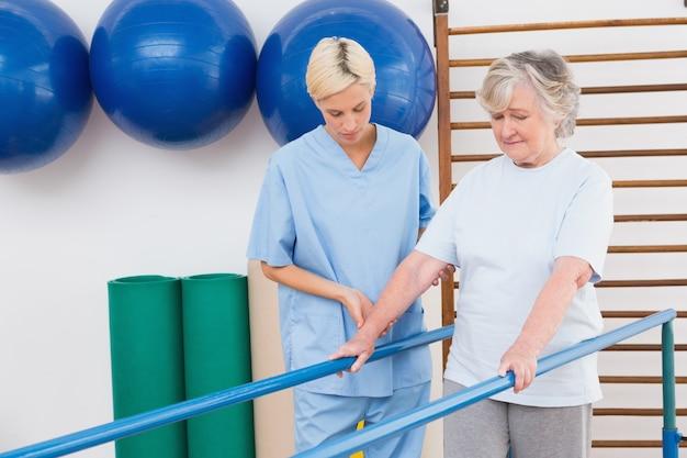 Ältere frau, die mit barren mit therapeuten geht