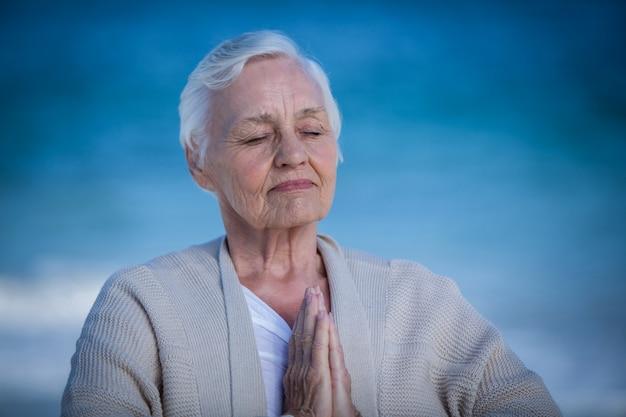 Ältere frau, die mit den verbundenen händen sich entspannt