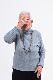 Ältere frau, die mit der hand auf gesicht auf weißem hintergrund späht
