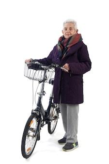 Ältere frau, die mit einem fahrrad auf weißem hintergrund aufwirft