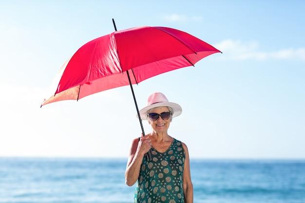 Ältere frau, die mit einem regenschirm aufwirft