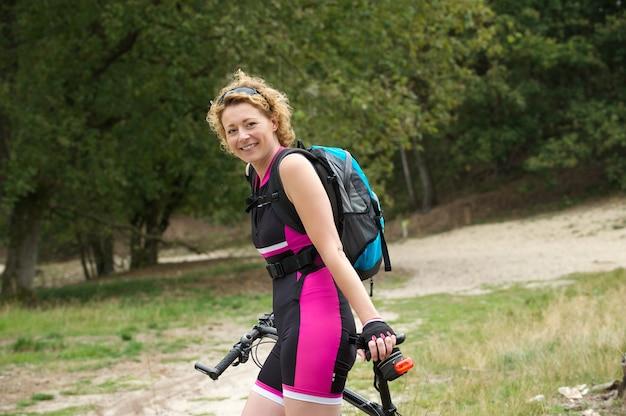Ältere frau, die mit fahrrad lächelt