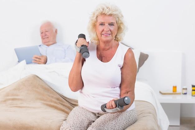 Ältere frau, die mit handgewichten trainiert