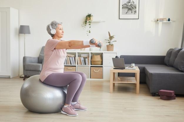 Ältere frau, die mit hanteln trainiert, während sie auf fitnessball sitzt und musik im raum zu hause hört