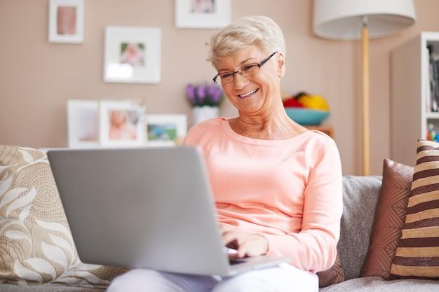 Ältere frau, die mit laptop auf sofa entspannt