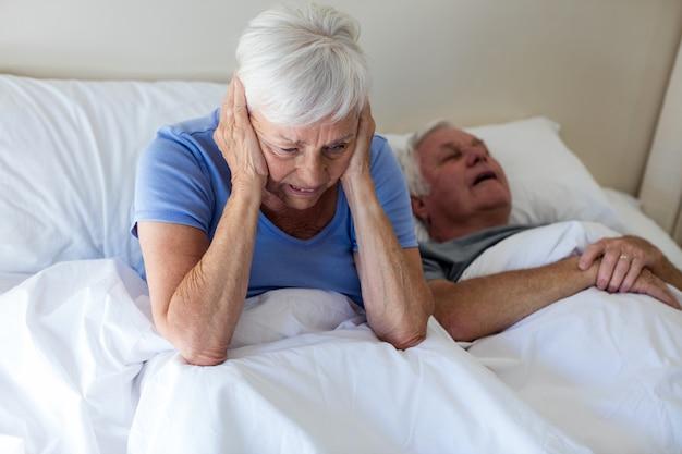 Ältere frau, die mit mann gestört wird, der auf bett im schlafzimmer schnarcht