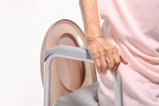 Ältere frau, die mobilen toilettensitzstuhl benutzt