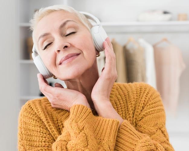 Ältere frau, die musik auf kopfhörern genießt