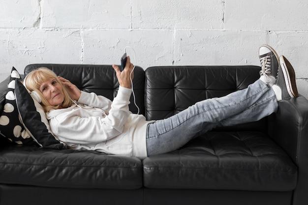 Ältere frau, die musik auf sofa zu hause hört