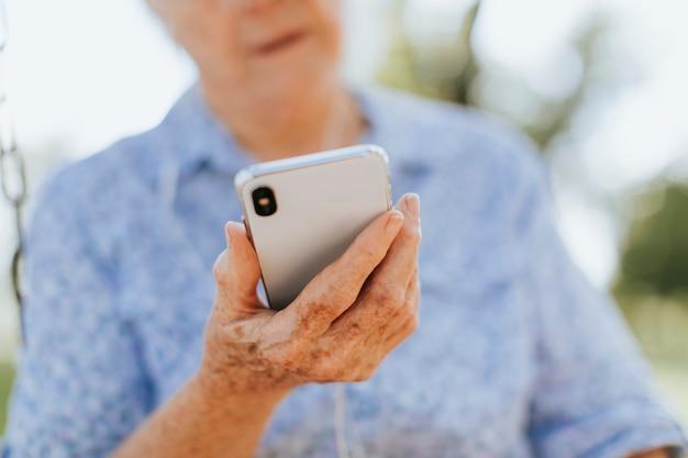 Ältere frau, die musik durch kopfhörer hört