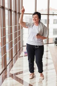 Ältere frau, die musik im fitnessstudio hört