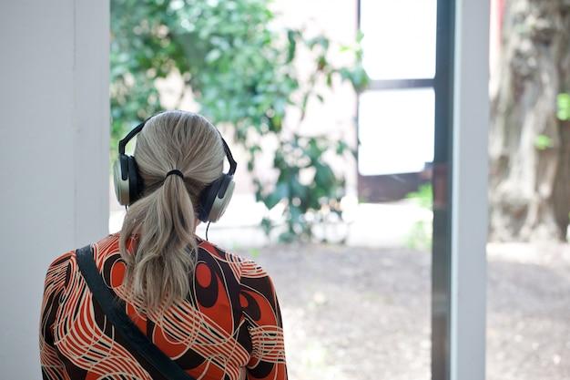 Ältere frau, die musik mit kopfhörern hört