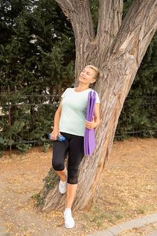 Ältere frau, die nach dem training gegen baum draußen ruht
