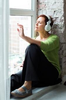 Ältere frau, die nahe bei einem fenster und einer hörenden musik sitzt
