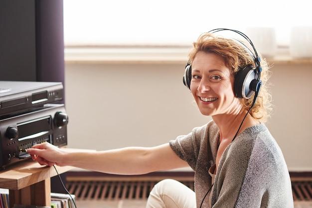 Ältere frau, die nahe bei soundsystem mit kopfhörern sitzt