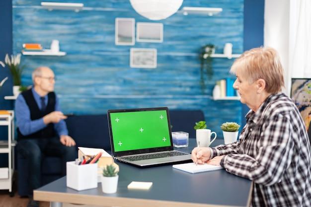Ältere frau, die notizen auf dem notebook macht und einen tragbaren computer mit verfügbarem kopienraum betrachtet