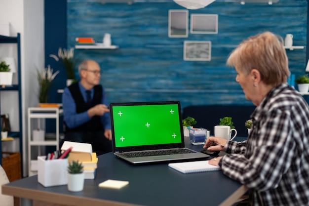 Ältere frau, die notizen über notebook macht, das tragbaren computer mit verfügbarem kopienraum betrachtet. ältere frau, die an laptop mit grünem bildschirm und ehemann arbeitet, der fernsehfernbedienung hält.