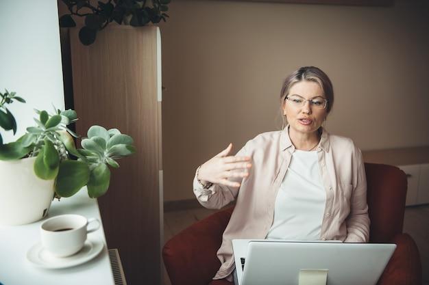 Ältere frau, die online-kurse auf laptop hat und etwas erklärt, das brille während der sperrung trägt