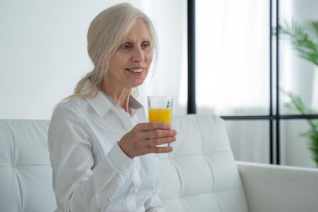 Ältere frau, die orangensaft trinkt, der auf der couch sitzt, alter menschenruhestand und gesunder lebensstil