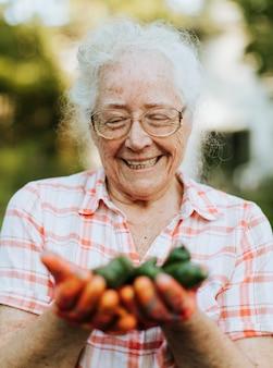 Ältere frau, die organischen jalapenopfeffer von ihrem eigenen garten hält