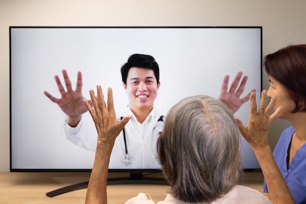 Ältere frau, die physiotherapie-onlinedienst zu hause verwendet.