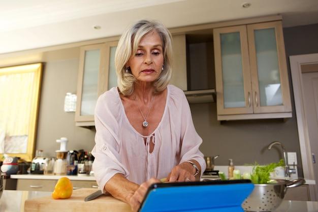 Ältere frau, die rezept in der küche auf tablette folgt