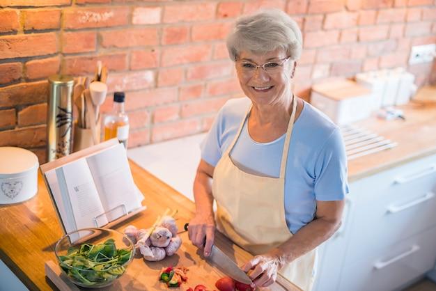 Ältere frau, die saisonales gemüse schneidet